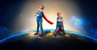 Les enfants dans des costumes de super héros gardent la planète photographie stock libre de droits