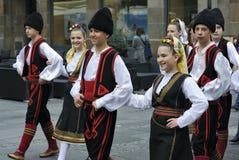 Les enfants dans des costumes nationaux marche par la ville Image stock