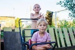 Les enfants dans la cour de la maison rurale, soeur de frère fait des klaxons Images libres de droits