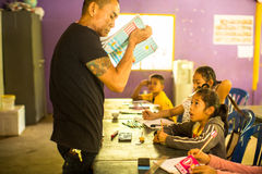 Les enfants dans la leçon à l'école par le Cambodgien de projet badine le soin pour aider les enfants déshérités Images libres de droits
