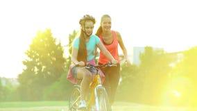 Les enfants dans le casque de bicyclette enseignent le vélo de tour en parc d'été banque de vidéos