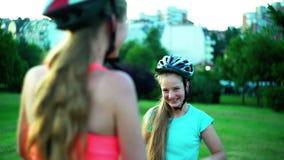 Les enfants dans le casque de bicyclette vont sur le vélo de promenade de colline banque de vidéos