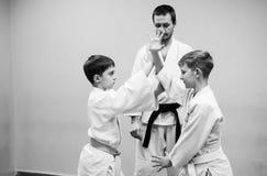 Les enfants dans le kimono commencent à s'exercer sur l'aikido images libres de droits