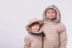 Les enfants dans le ` s d'apiculteur adapte à la pose à l'arrière-plan de blanc de studio photo stock