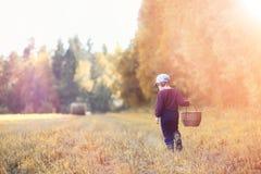 Les enfants dans le village marchent par la forêt et le gathe d'automne photographie stock