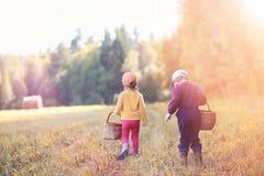 Les enfants dans le village marchent par la forêt et le gathe d'automne image stock