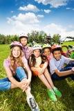 Les enfants dans les casques rient, s'asseyent ensemble sur l'herbe Photo stock