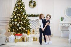 Les enfants dansent près de l'arbre de Noël décoré ayant joint des mains photos stock