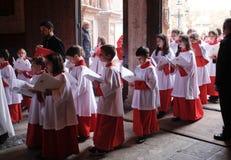 Les enfants de choeur entrent dans l'église pendant une masse de Pâques de semaine sainte en île de Majorque image stock