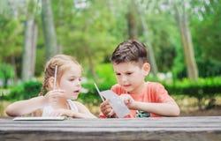Les enfants de Hapy apprennent en parc Le frère et la soeur font ensemble le j Photographie stock