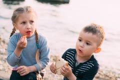 Les enfants de la mer mangent du pain de fille et de gar?on de tomate grill? image stock