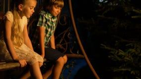 Les enfants de mêmes parents amicaux appréciant l'oscillation confortable montent, passant des vacances d'été ensemble banque de vidéos