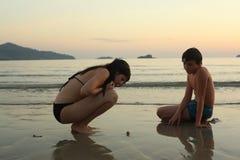 Les enfants de mêmes parents d'adolescent sur le bord de la mer échouent rechercher des morceaux de crabe et de corall de coquill Photos libres de droits