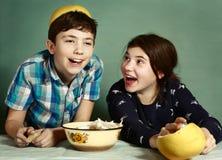 Les enfants de mêmes parents d'enfants épluchant le fruit de raisin font le chapeau drôle Images libres de droits