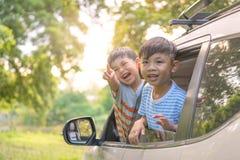 Les enfants de mêmes parents heureux ondulant des mains voyagent en voiture contre le ciel bleu Concept de voyage par la route d' image libre de droits