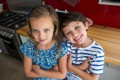 Les enfants de mêmes parents heureux se tenant avec des bras ont croisé dans la cuisine Image stock