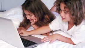 Les enfants de mêmes parents mignons à l'aide de l'ordinateur portable sur leurs parents enfoncent banque de vidéos
