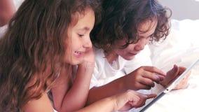 Les enfants de mêmes parents mignons à l'aide du comprimé sur leurs parents enfoncent banque de vidéos