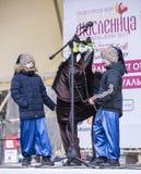 Les enfants de Maslenitsa- ainsi qu'un cheval décoratif chantent au Th Images stock