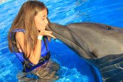 Les enfants de petite fille embrassant un enfant heureux de sourire de visage de nageoire magnifique de dauphin nagent des dauphi Photographie stock libre de droits