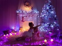 Les enfants de pièce de nuit de Noël sous l'arbre de lumières, filles d'enfants autoguident Photo stock