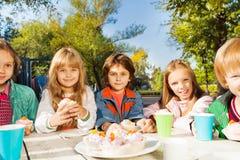 Les enfants de sourire reposent la fin à la table blanche en bois Photo stock