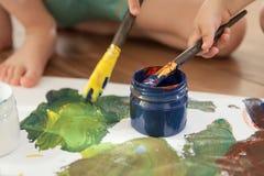 Les enfants dessinent une gouache colorée sur une grande feuille de papier image stock