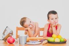Les enfants drôles de famille heureuse préparent la tarte aux pommes, sur un fond blanc Photographie stock