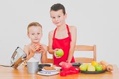 Les enfants drôles de famille heureuse préparent la tarte aux pommes, sur un fond blanc Photo stock