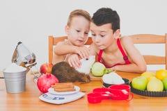 Les enfants drôles de famille heureuse préparent la tarte aux pommes, sur un fond blanc Image stock