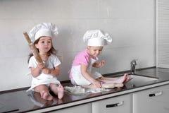 Les enfants drôles préparent la pâte dans la cuisine Famille heureux photographie stock