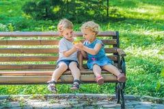 Les enfants en bas âge garçon et fille s'asseyant sur un banc par la mer et mangent un a Images libres de droits