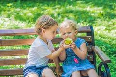 Les enfants en bas âge garçon et fille s'asseyant sur un banc par la mer et mangent un a Photos stock