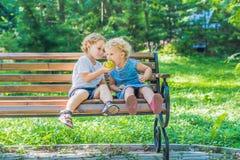 Les enfants en bas âge garçon et fille s'asseyant sur un banc par la mer et mangent un a Photographie stock libre de droits