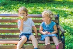 Les enfants en bas âge garçon et fille s'asseyant sur un banc par la mer et mangent un a Image stock
