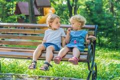 Les enfants en bas âge garçon et fille s'asseyant sur un banc par la mer et mangent le brea Photos stock