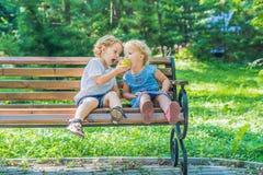 Les enfants en bas âge garçon et fille s'asseyant sur un banc par la mer et mangent une pomme Image libre de droits