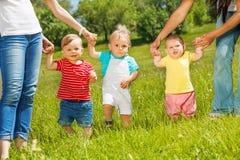 Les enfants en bas âge heureux apprennent à marcher tenant des mains de mères photos libres de droits