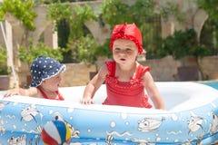 Les enfants en bas âge heureux joue dehors dans une piscine de bébé Image libre de droits