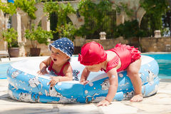 Les enfants en bas âge heureux joue dehors dans une piscine de bébé Image stock