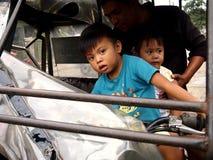Les enfants en bas âge monte un tricycle sur le siège du ` s de conducteur Image libre de droits