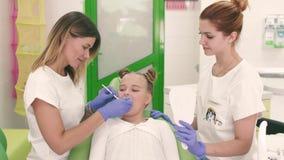 Les enfants et la femme de dentiste de famille regardant des dents dans votre bouche ont une belle, petite fille Se reposer à côt banque de vidéos