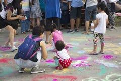 Les enfants et le parent thaïlandais voyagent et jouent la couleur de poudre de peinture sur la terre Image libre de droits