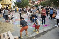 Les enfants et le parent thaïlandais voyagent et jouent la couleur de poudre de peinture sur la terre Photo stock