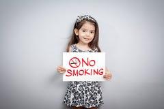 Les enfants feignent tenir un signe non-fumeurs photo stock