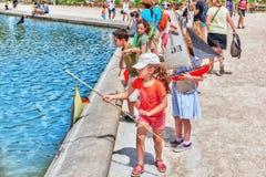 Les enfants flottent des bateaux dans le palais du luxembourgeois de fontaine Photos libres de droits