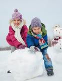 Les enfants font un bonhomme de neige Photo libre de droits