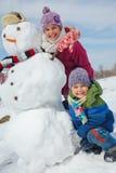 Les enfants font un bonhomme de neige Photos stock