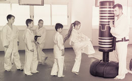 Les enfants formant le karaté donne un coup de pied sur le sac de sable pendant le cla de karaté images libres de droits