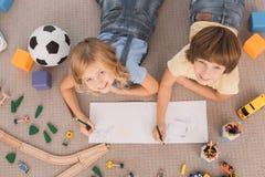 Les enfants frère et la famille de soeur chronomètrent ensemble à l'intérieur Photographie stock